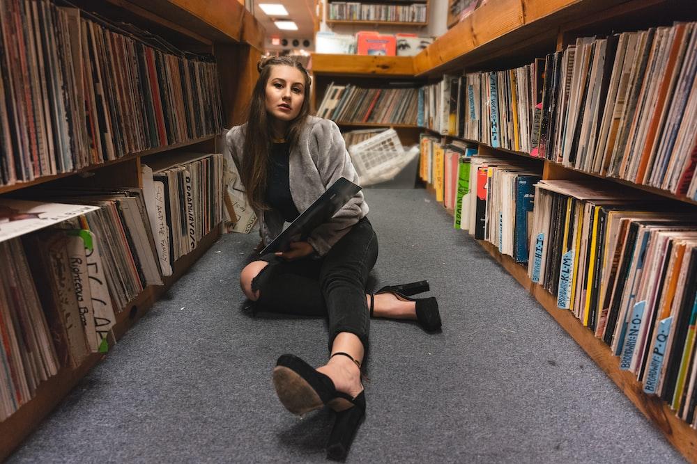 woman sitting on floor between bookshelves