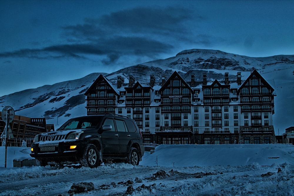 SUV parked in front building with mountain background