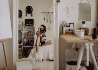 woman taking selfie while sitting on white pad