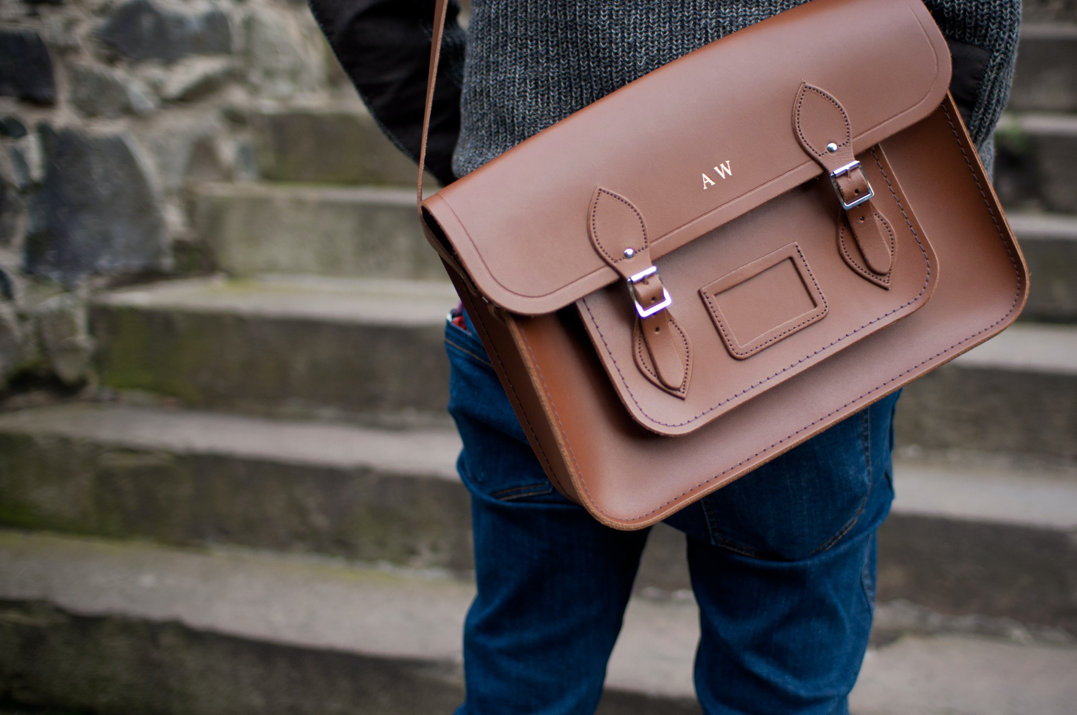 person carrying brown leather shoulder bag