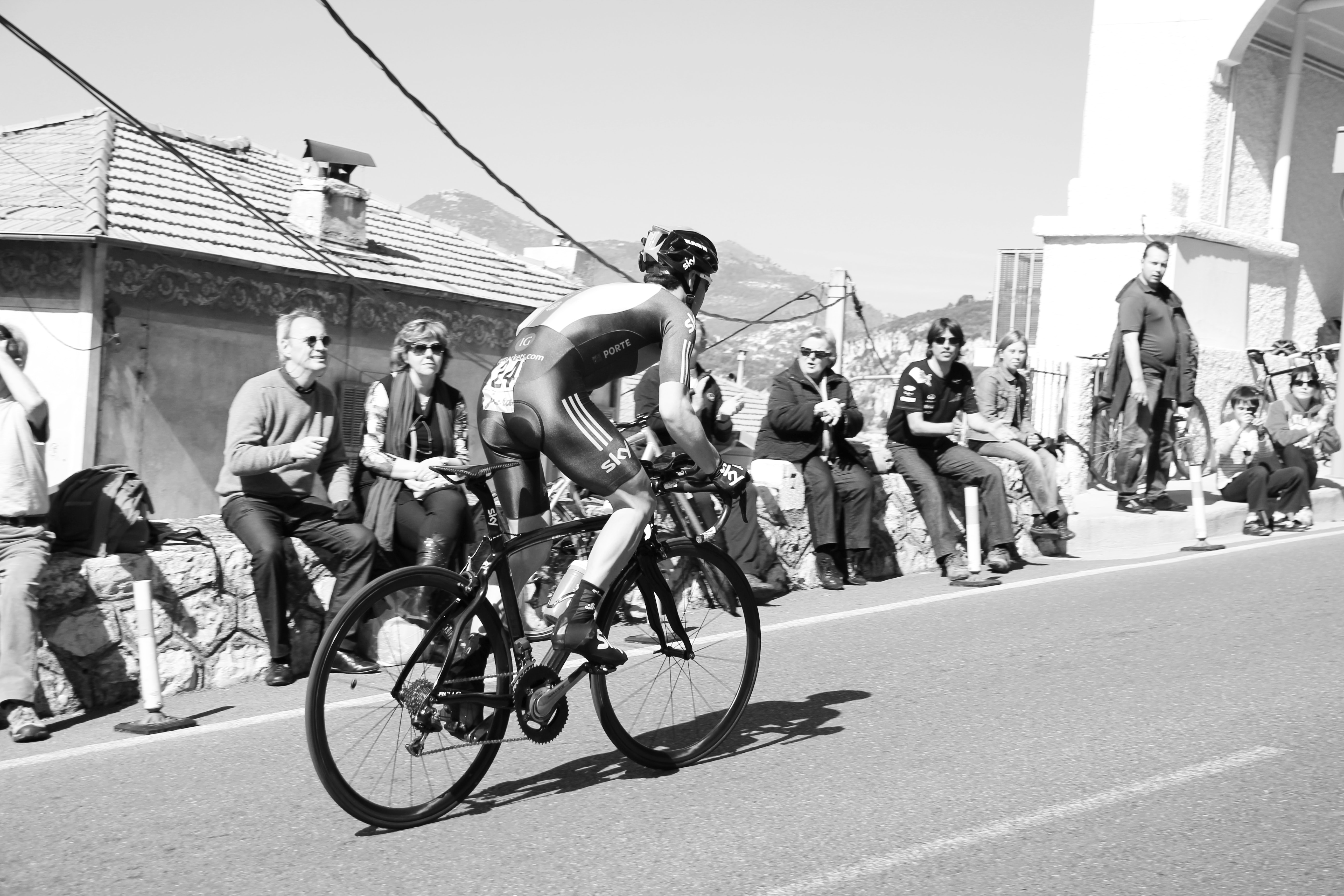 grayscale photo of cyclist on uphill road