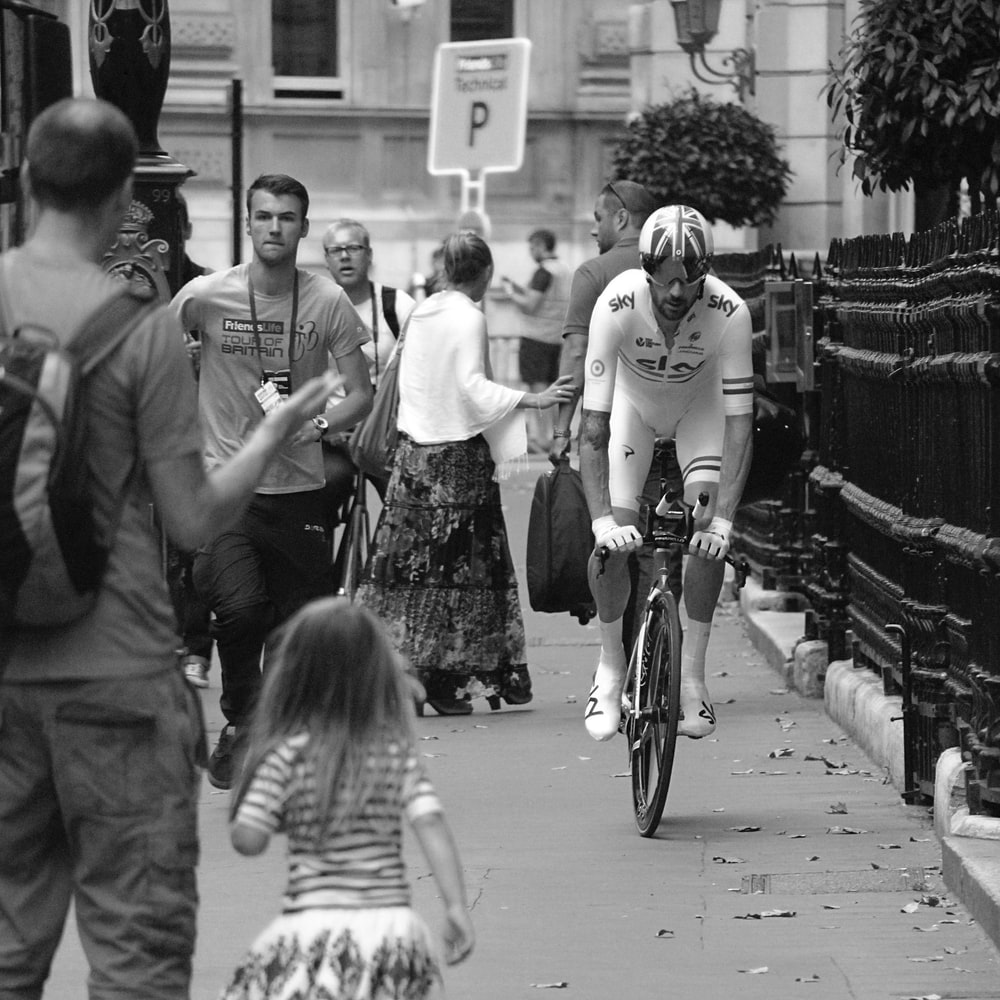 grayscale photo of man cycling beside group of people