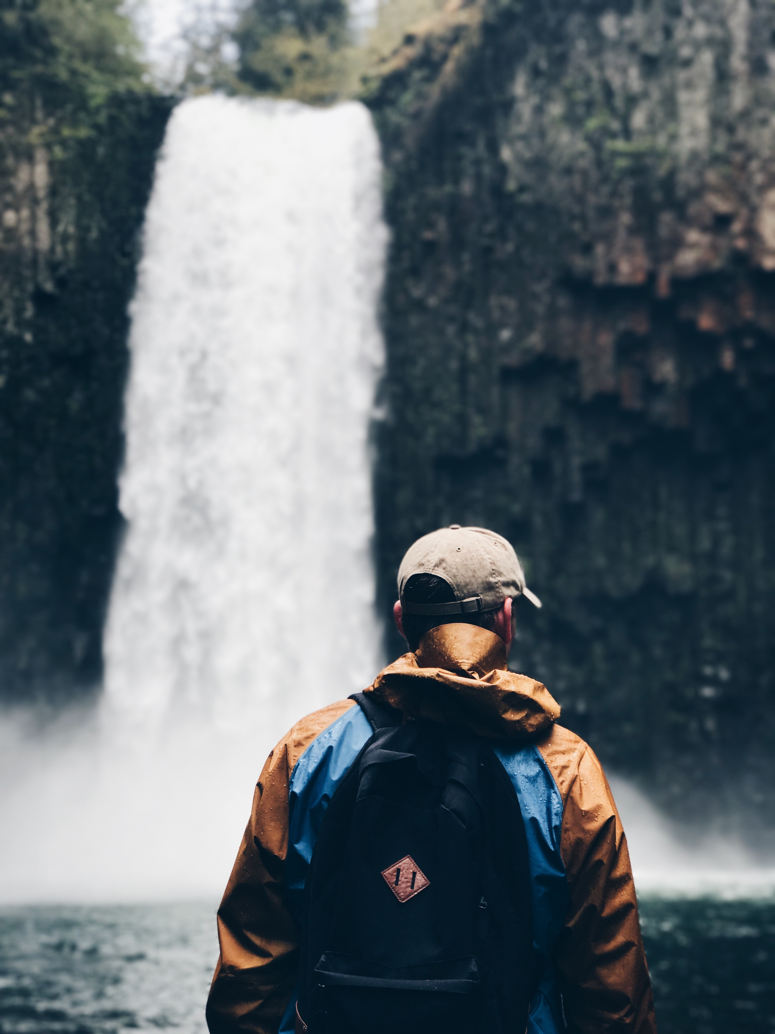 selective focus photography of man standing on waterfalls