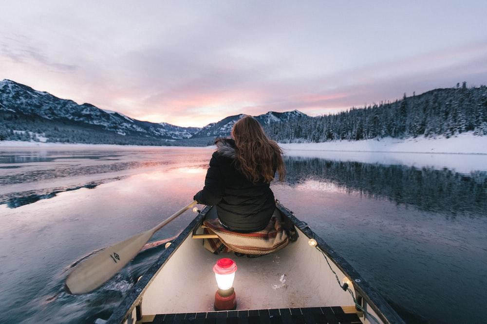 woman wearing black winter jacket sitting on boat paddling toward mountains