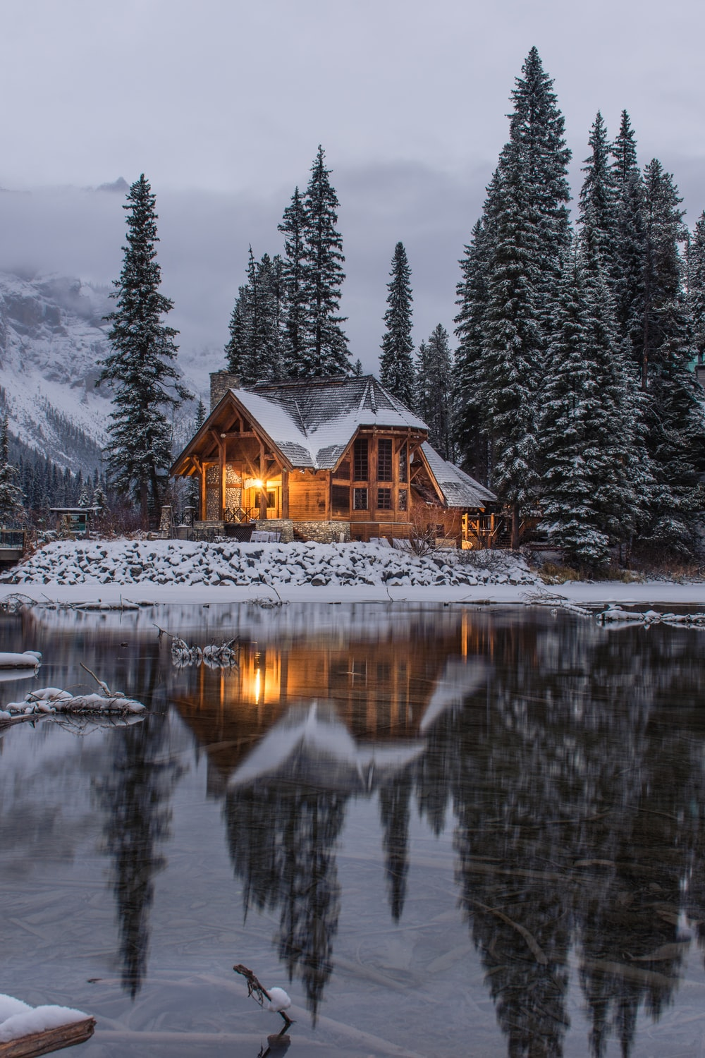 wooden house near pine trees and pond coated with snow during daytime