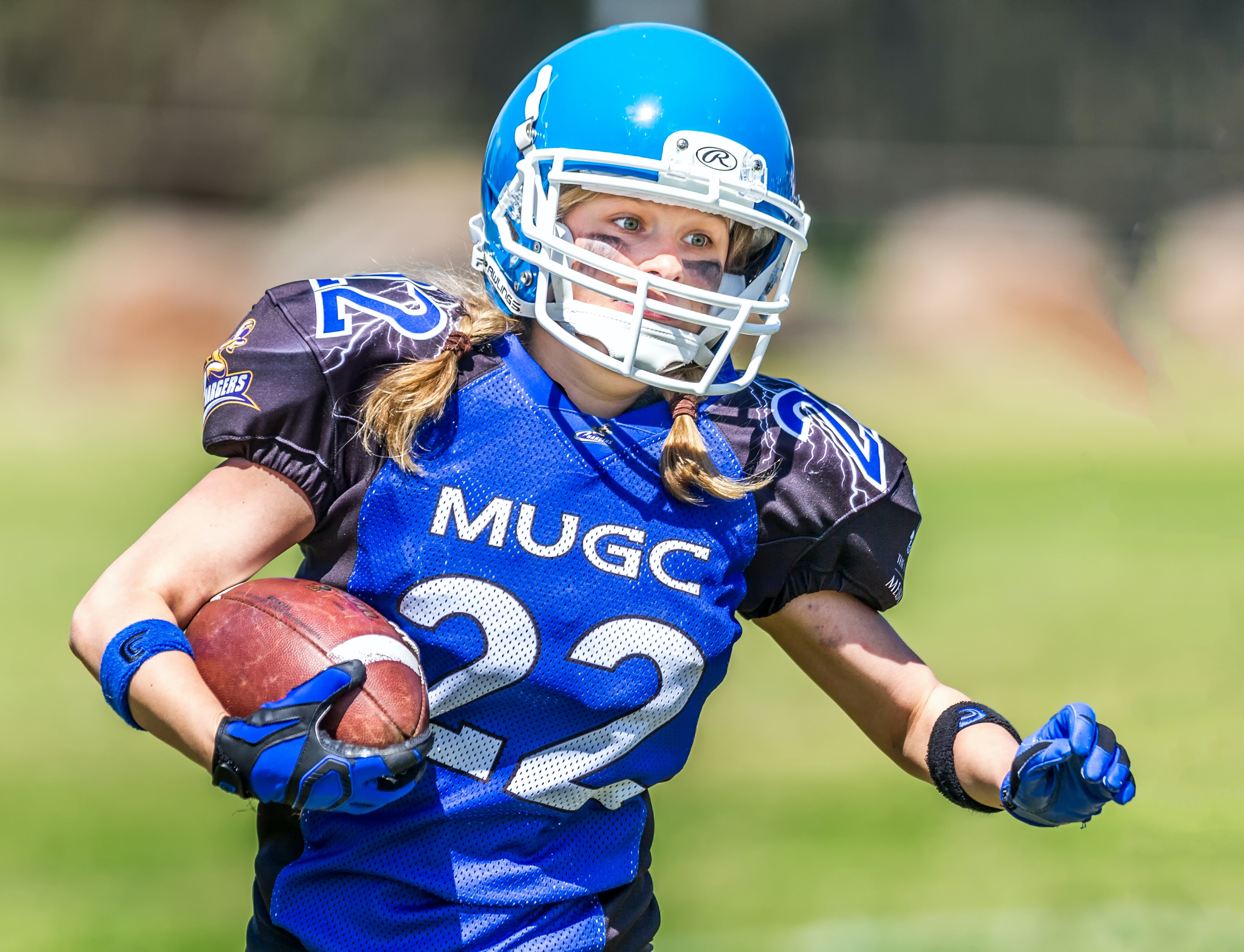 woman in blue helmet playing football