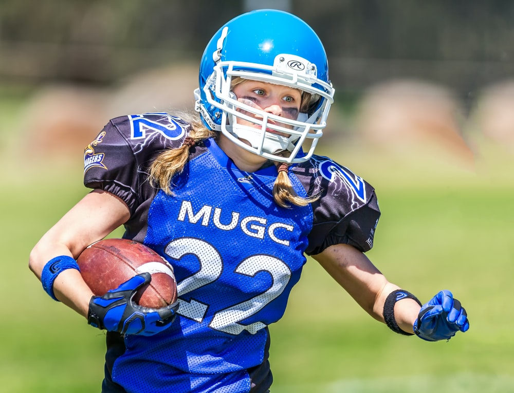 woman in blue helmet playing football