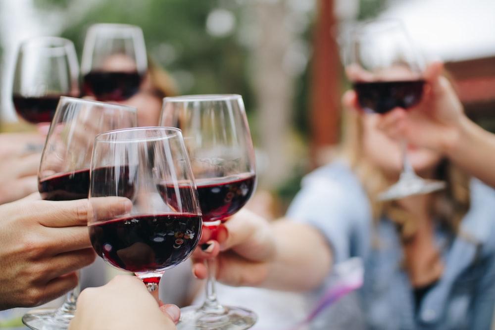 people tossing their clear wine glasses degustazione vini milano