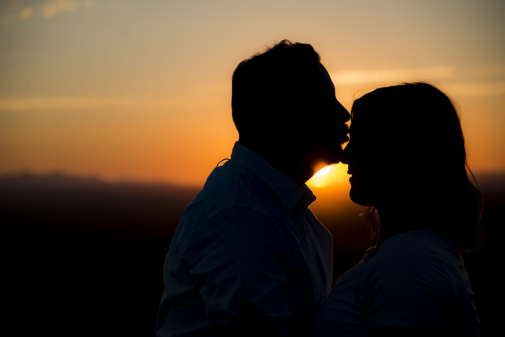 silhouette of man kissing woman's forehead