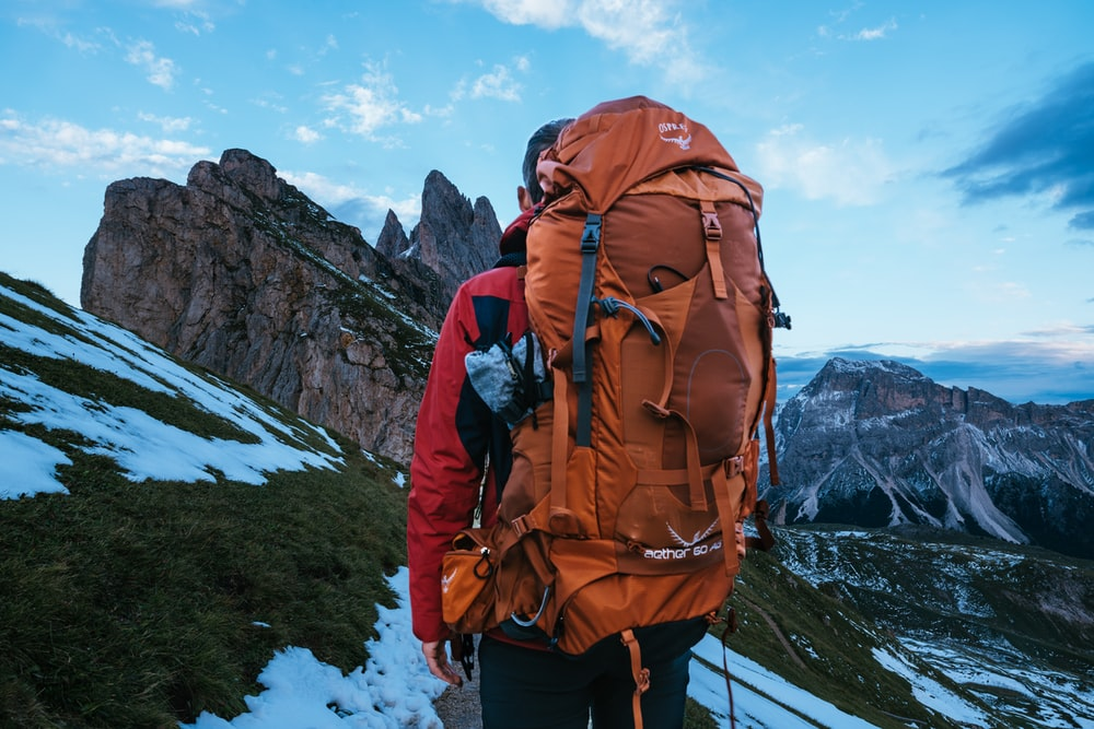 man carrying backpack standing on mountain during daytime