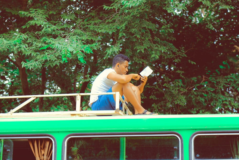 man reading notes on top of vehicle