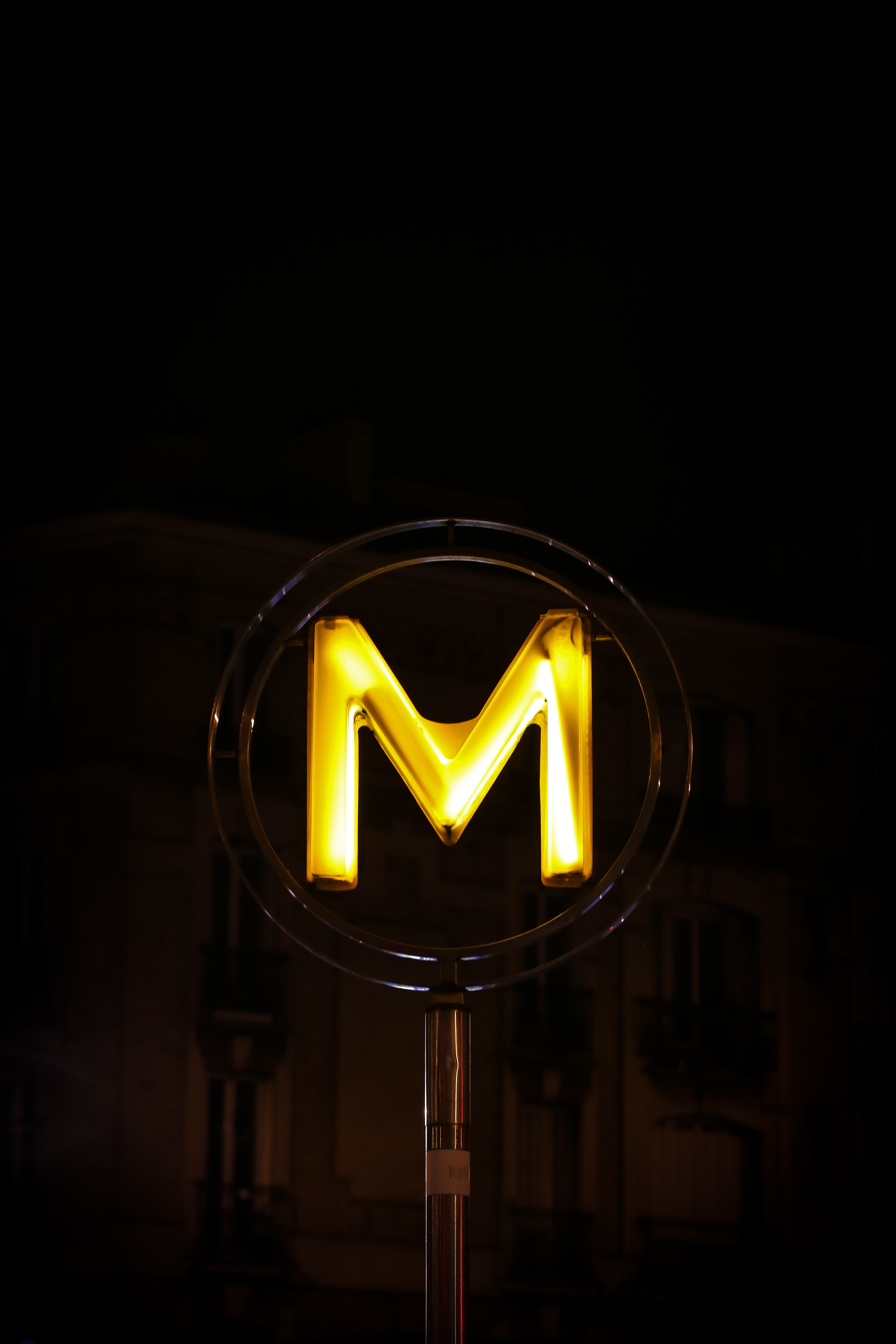 closeup photo of orange M neon signage