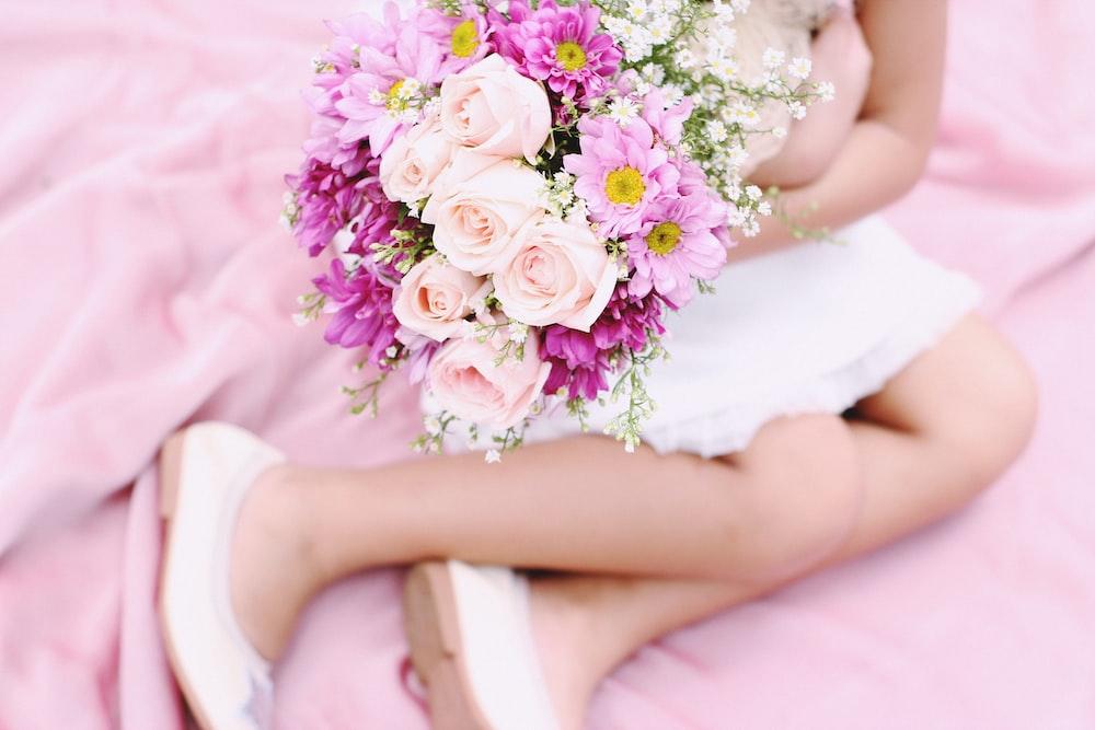 girl sitting on pink textile