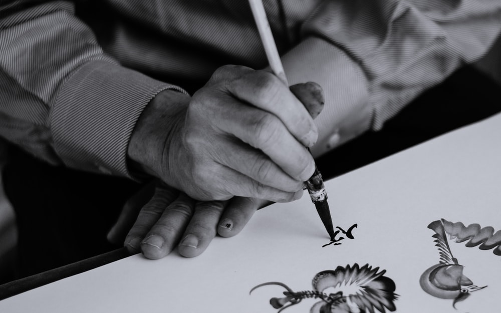 gray scale photo of person holding ink pen