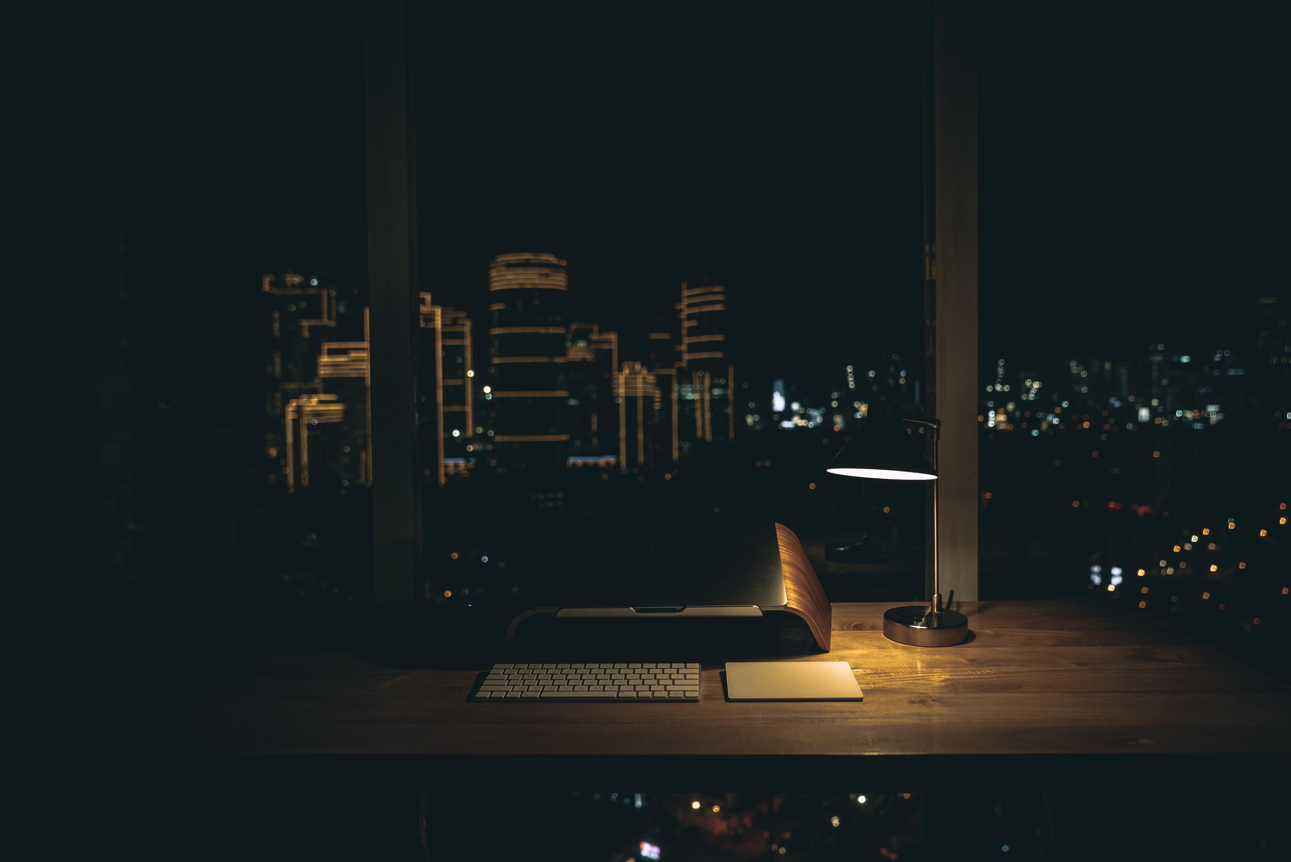 lit desk lamp on top of desk