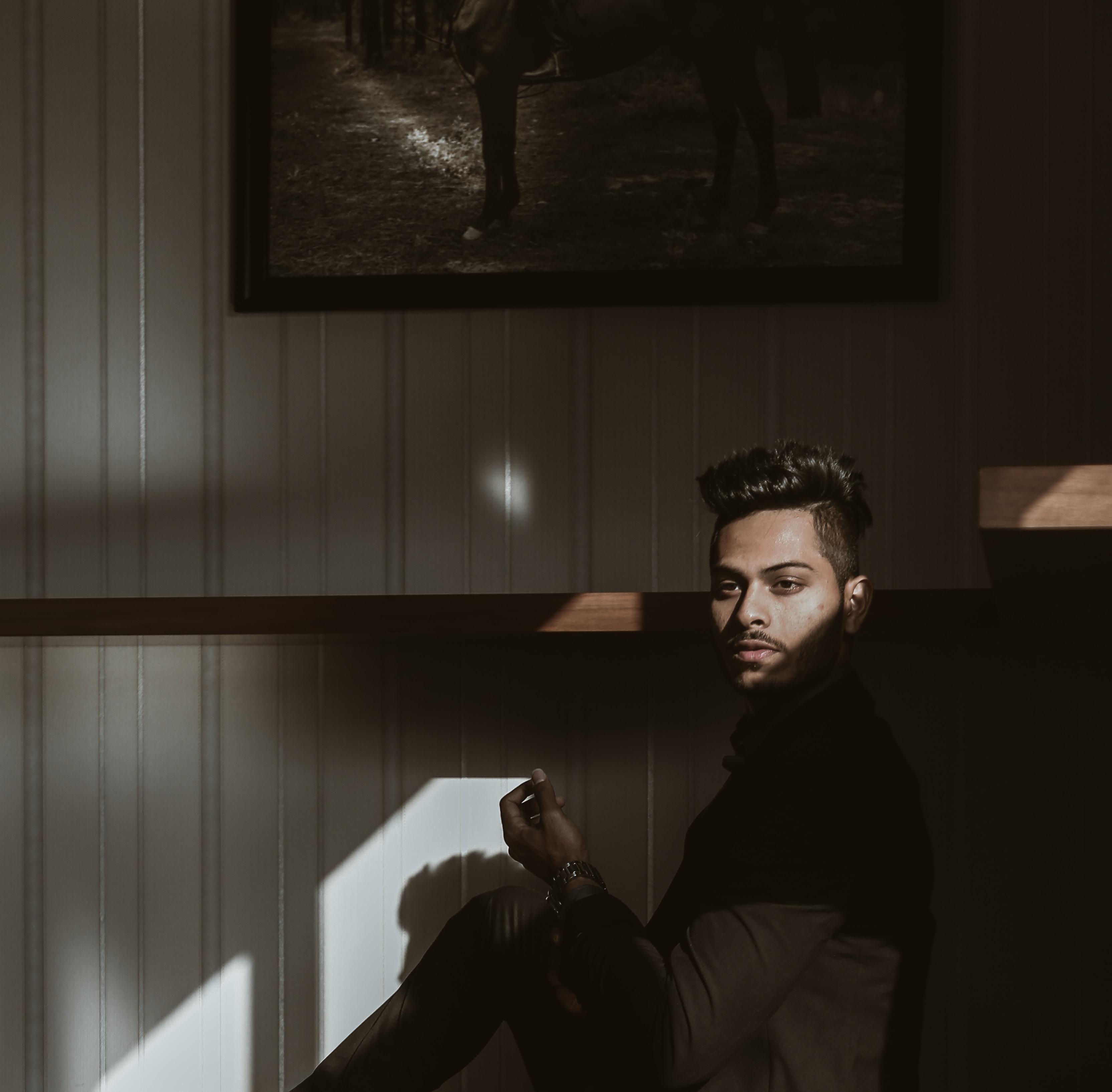 man sitting beside painting