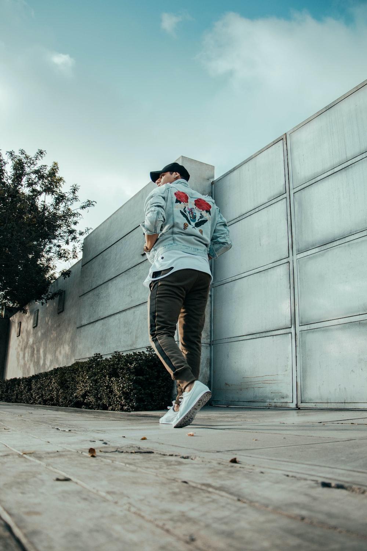 man walking near gray concrete wall at daytime