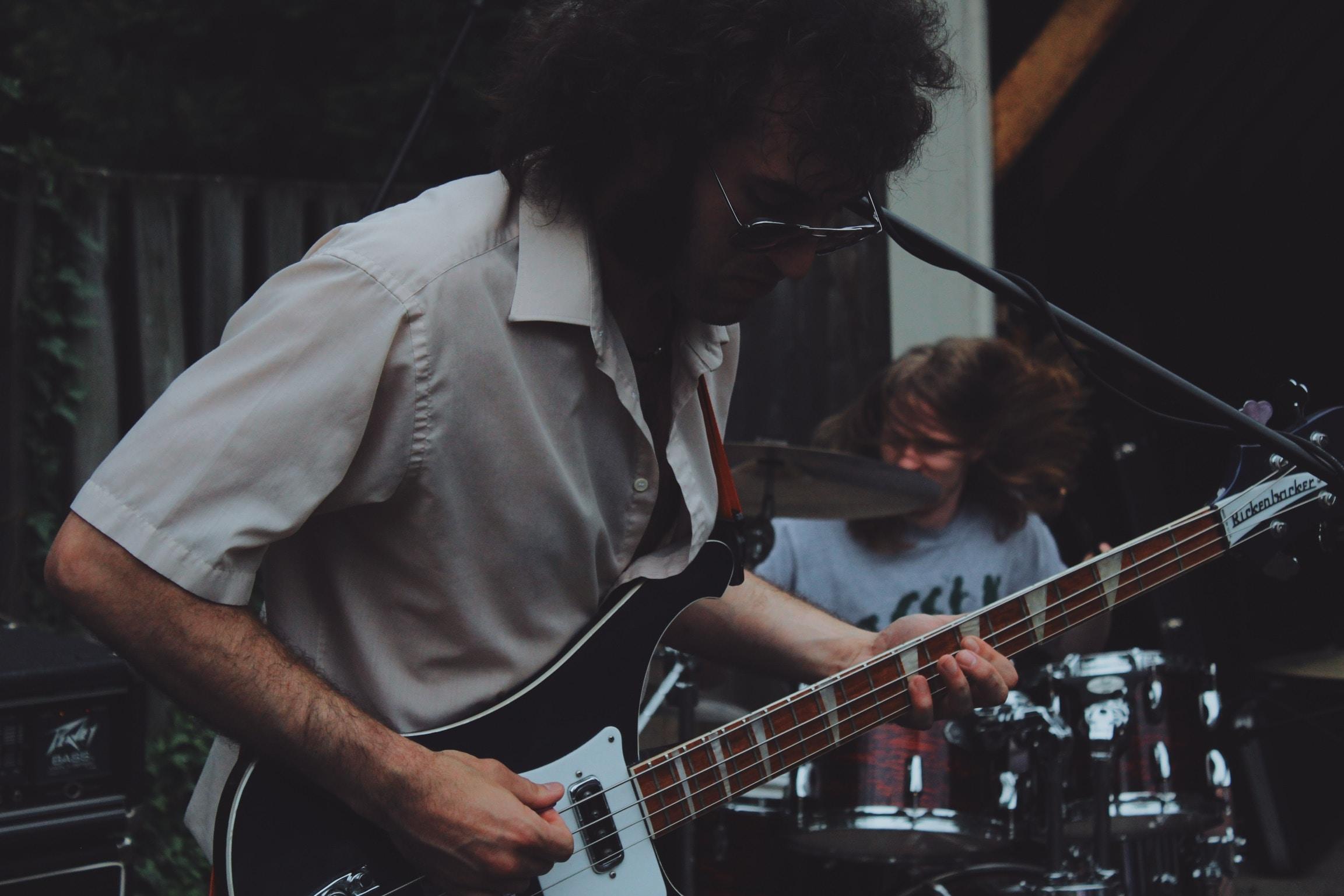 man playhing guitar beside man playing drums