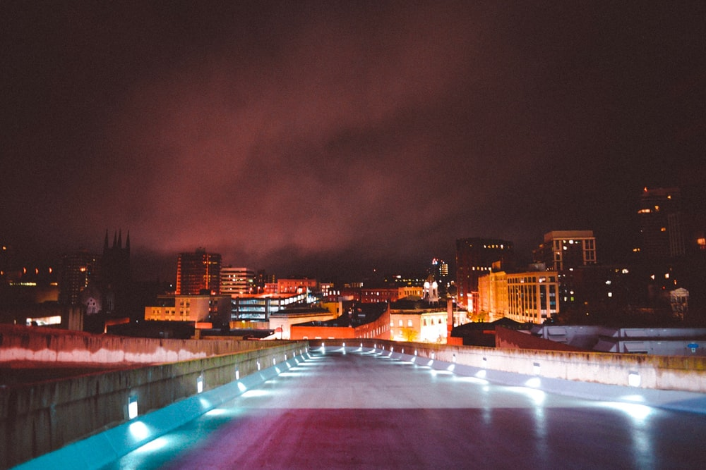 landscape photography of lighted road leading to city