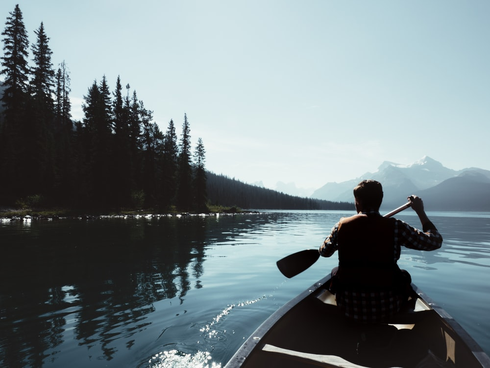man on canoe sailing on the river