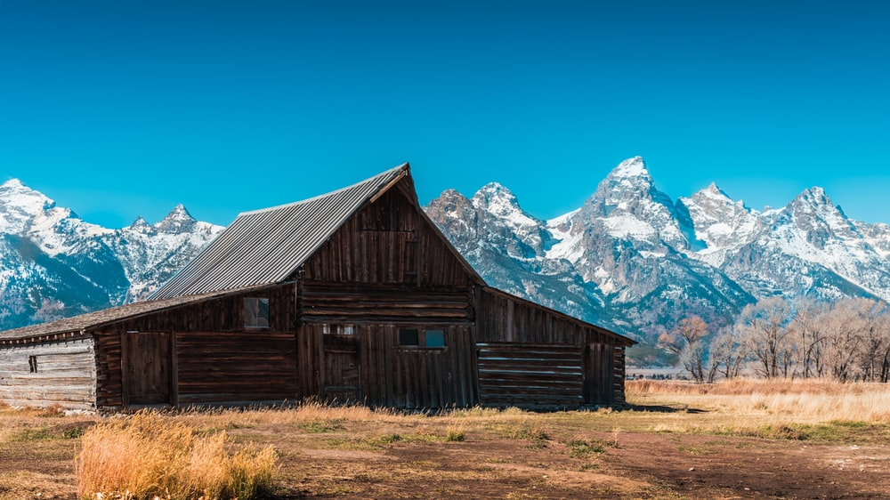 brown wooden house near gray and white snowed mountains