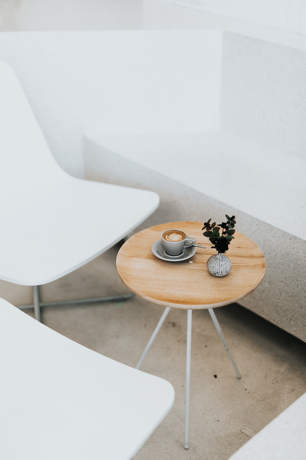 round brown table beside two white chairs