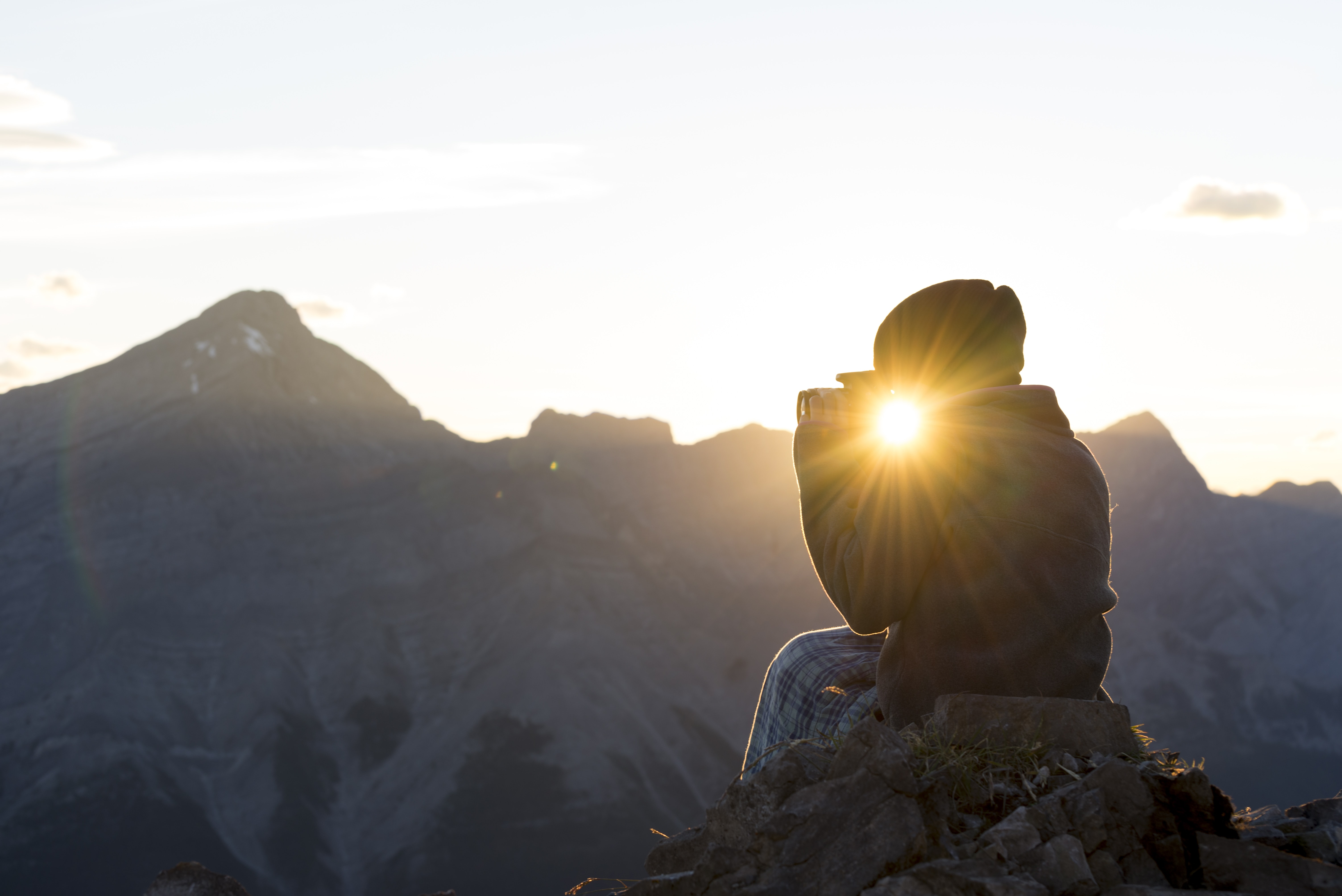 silhouette photography of person seating on rock in front of mountains