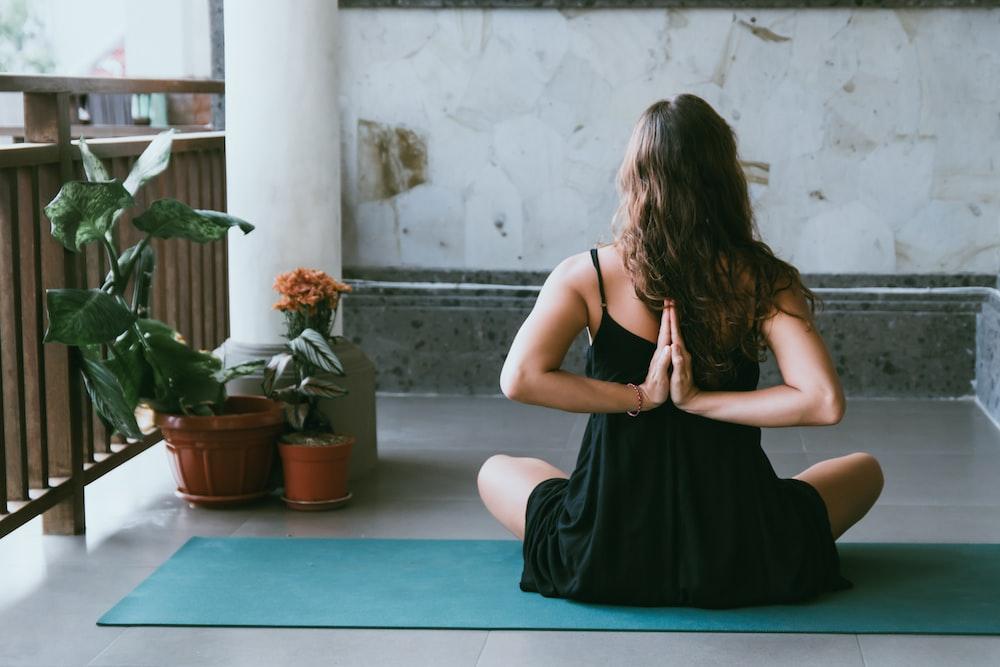 woman wearing black shirt sitting on green yoga mat