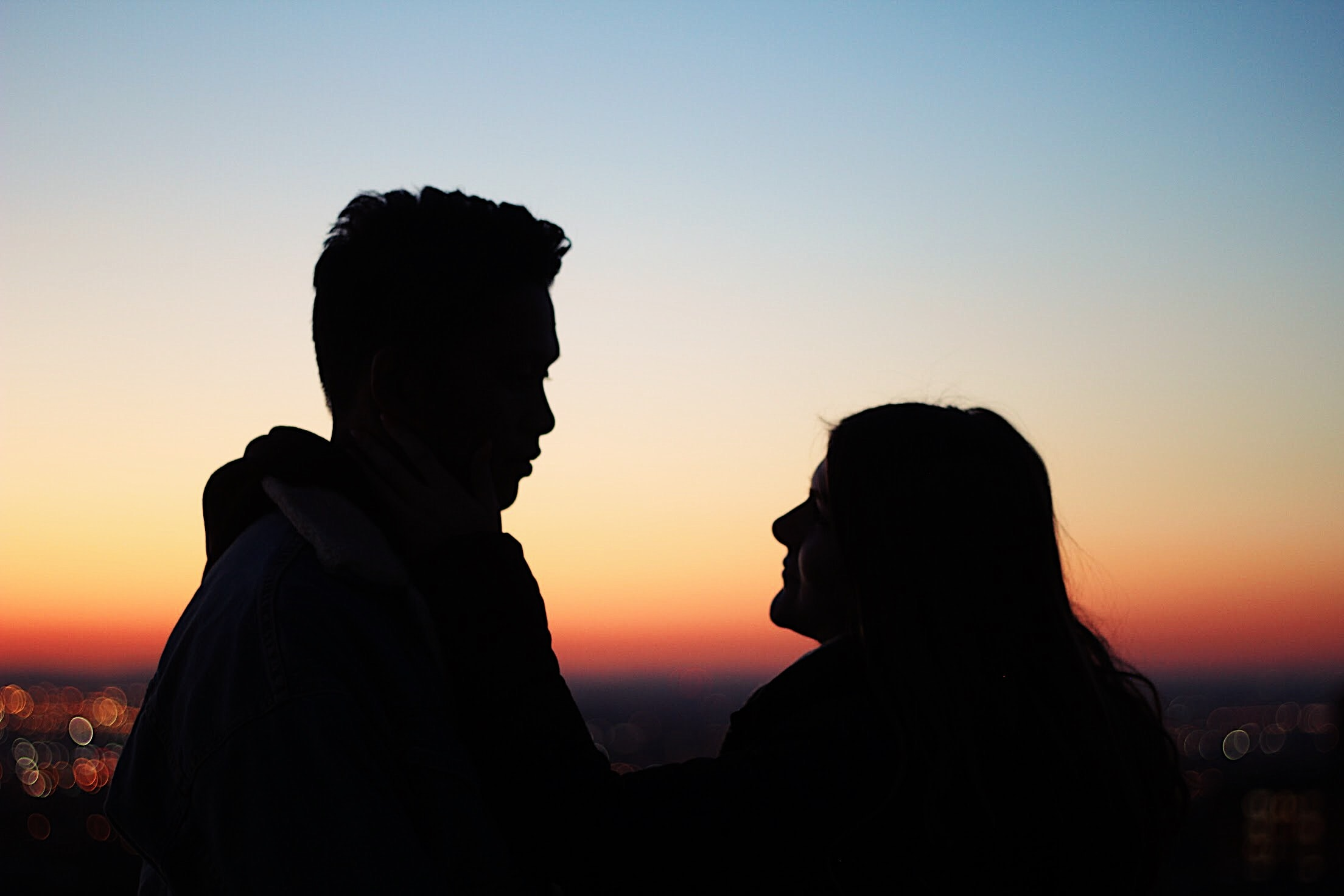 silhouette of man standing beside woman facing each other
