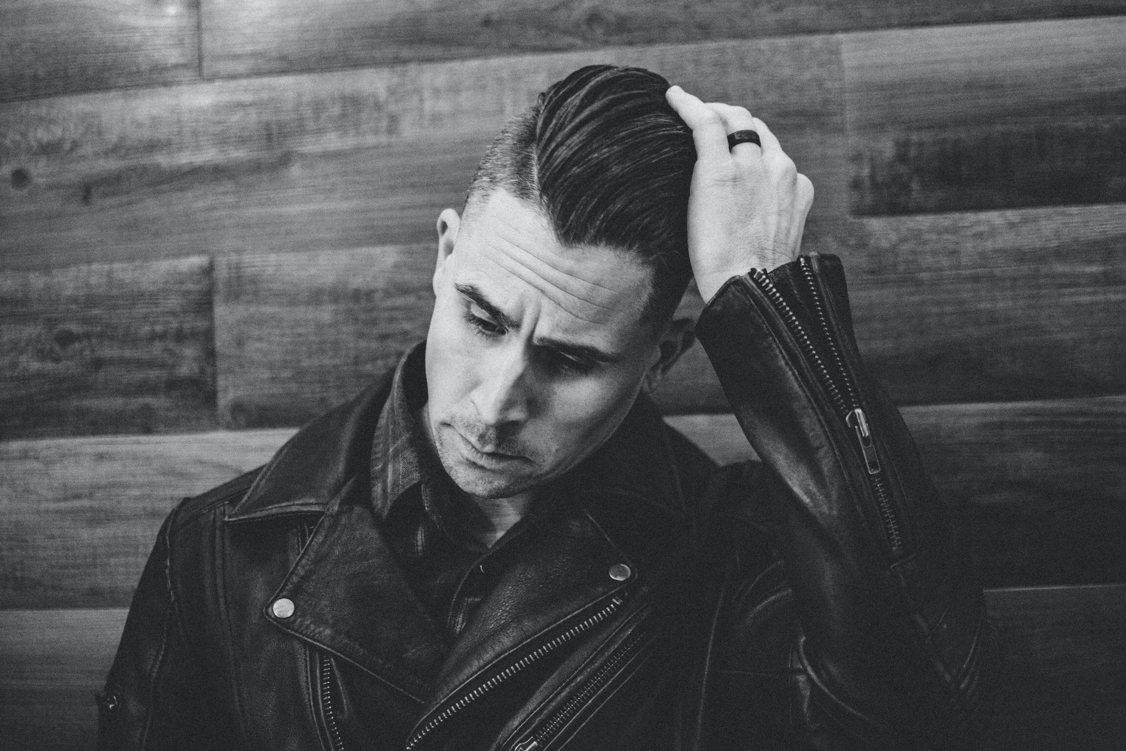 grayscale photography of man wearing leather jacket leaning against wall while fixing hair