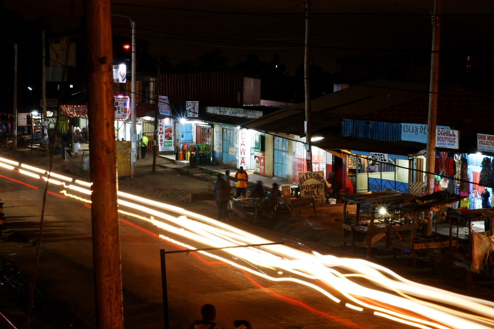 time lapse photography of race car lights on road beside stores