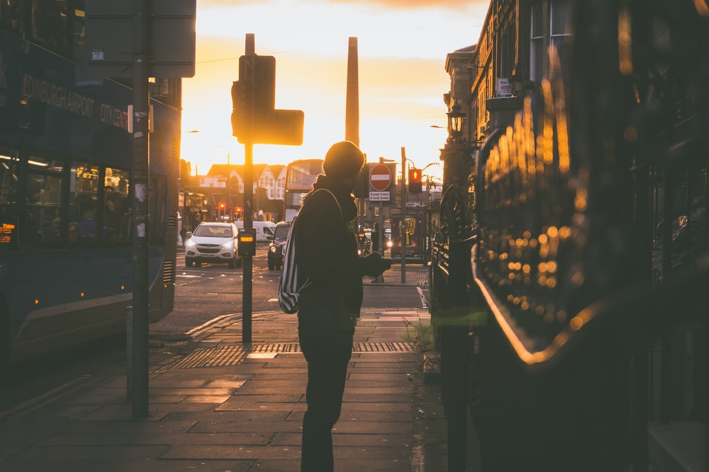 silhouette photography of man standing in front of building