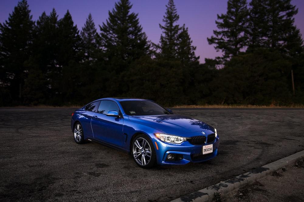 blue BMW coupe on brown asphalt road