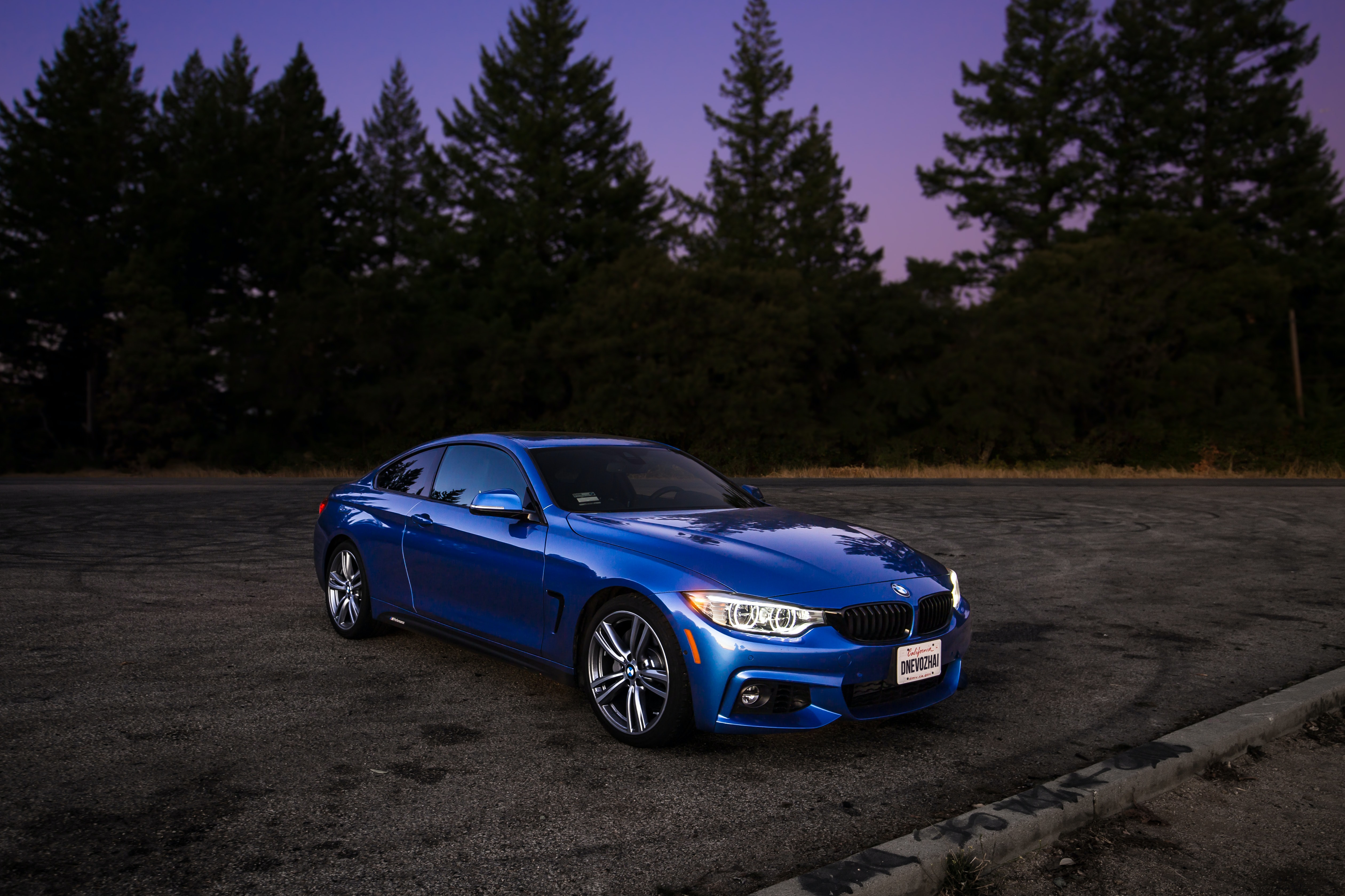 blue BMW coupe on brown asphalt road