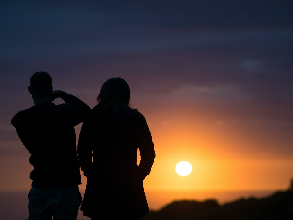man and woman silhouettes during golden hour