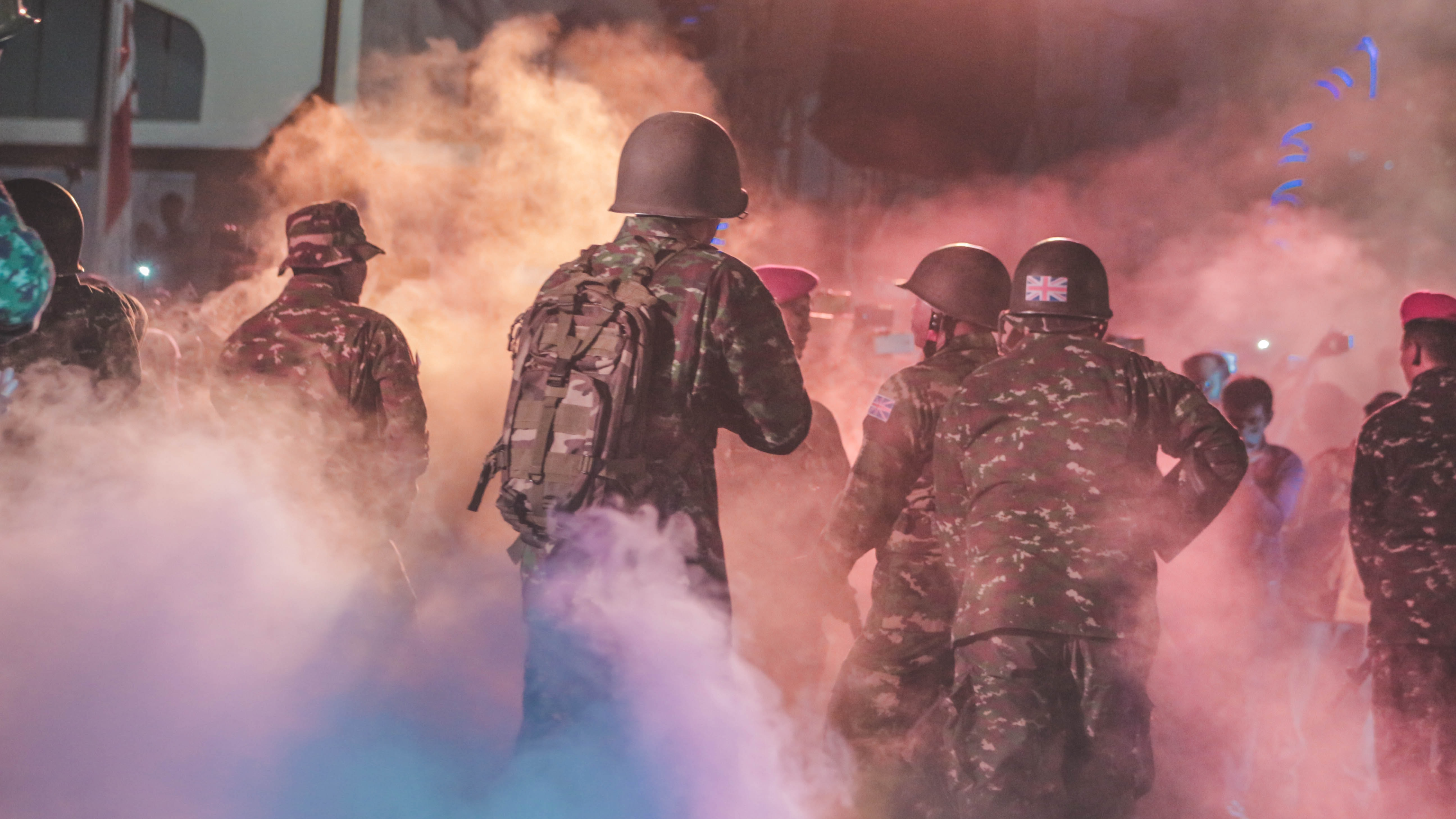 soldiers against crowd of people with smoke trail