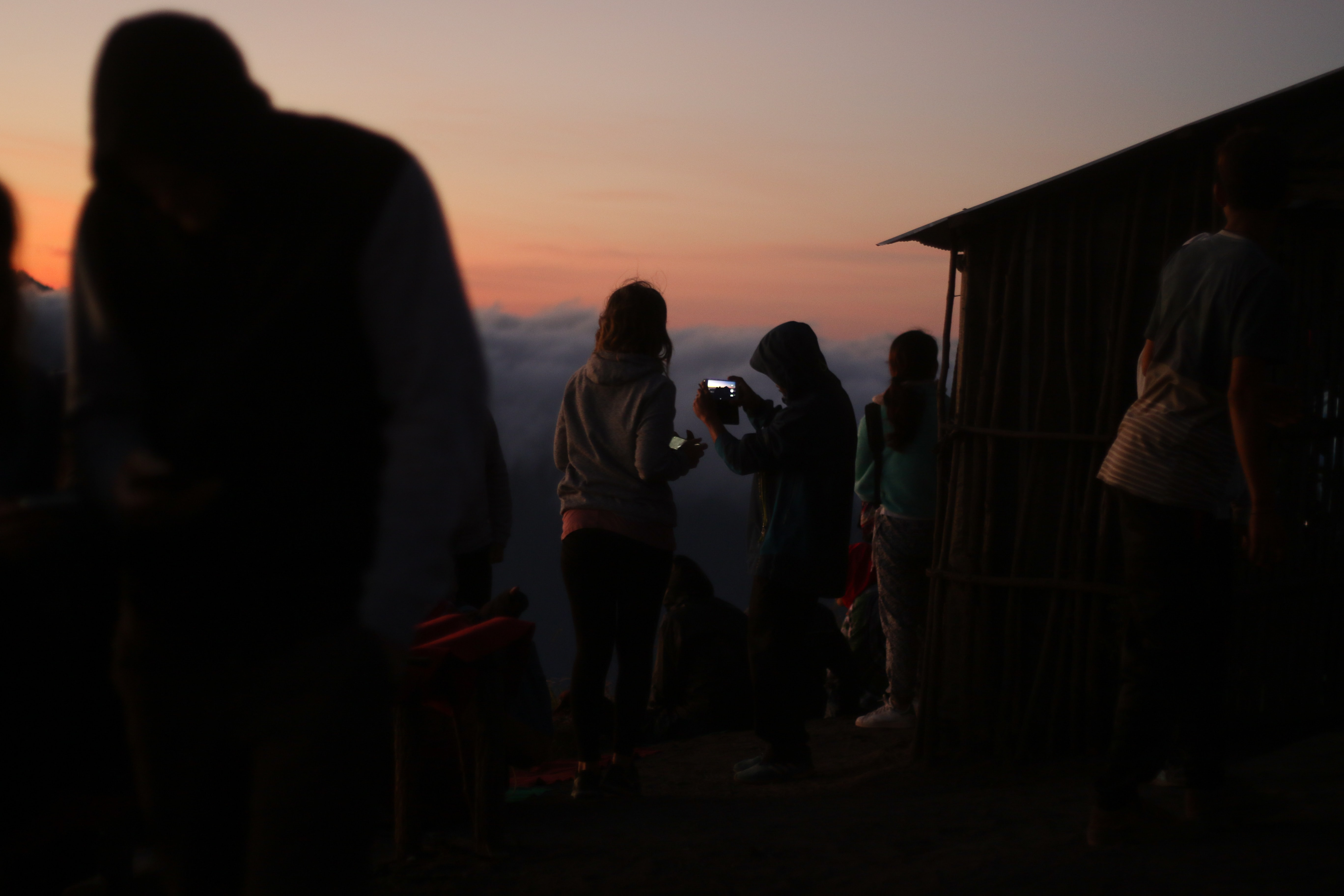 group of people near hut at sunset