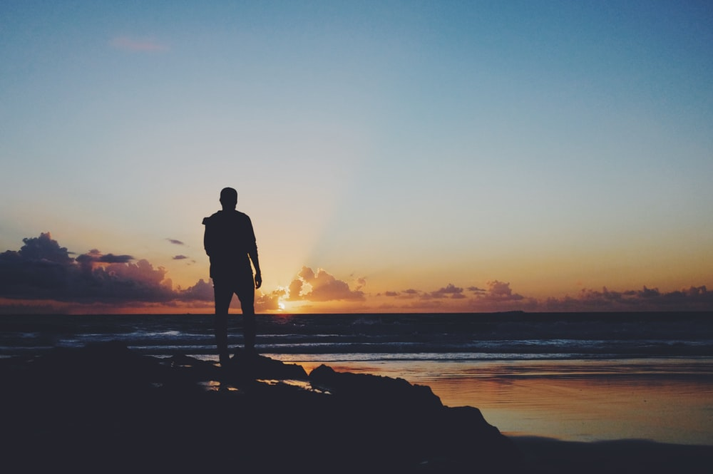 silhouette of man standing near shoreline