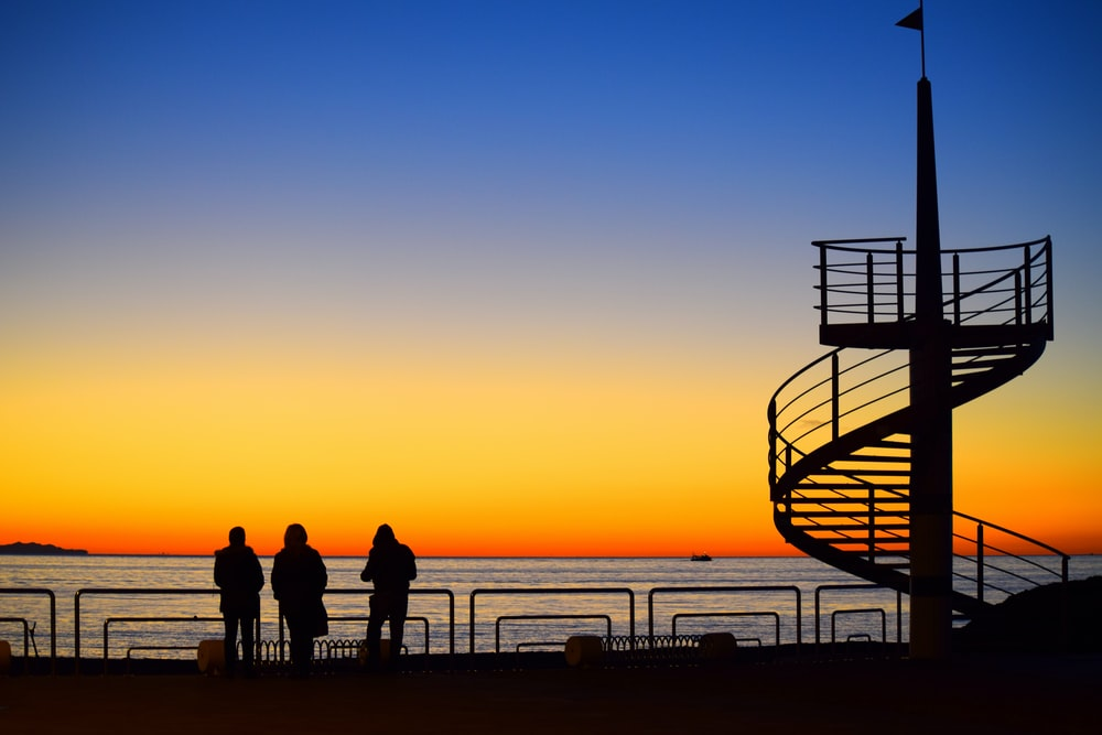 three person watching sunset