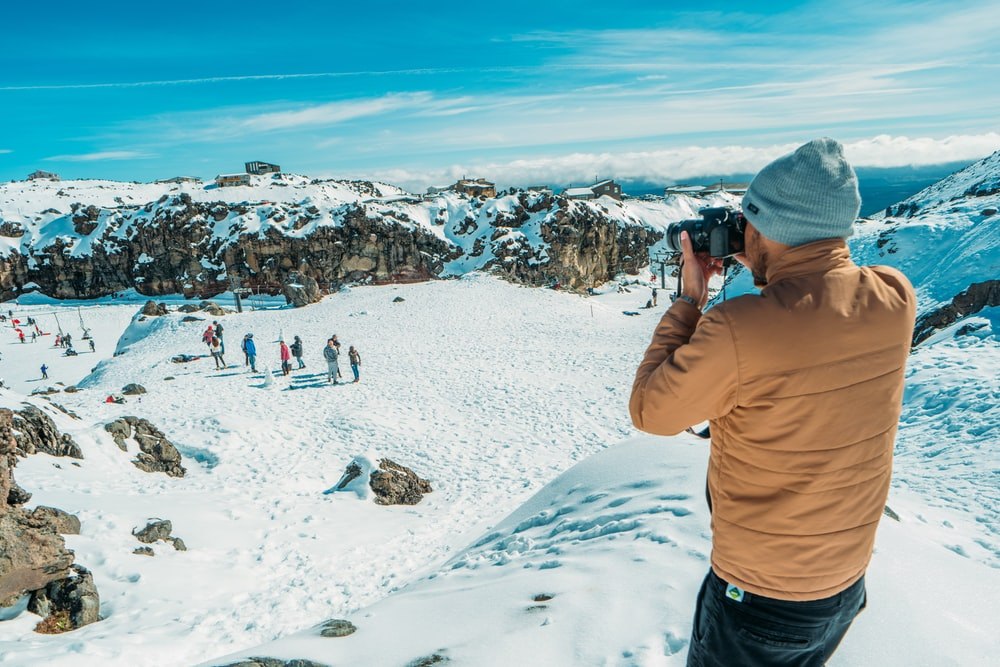 man standing on glacier mountain taking photo