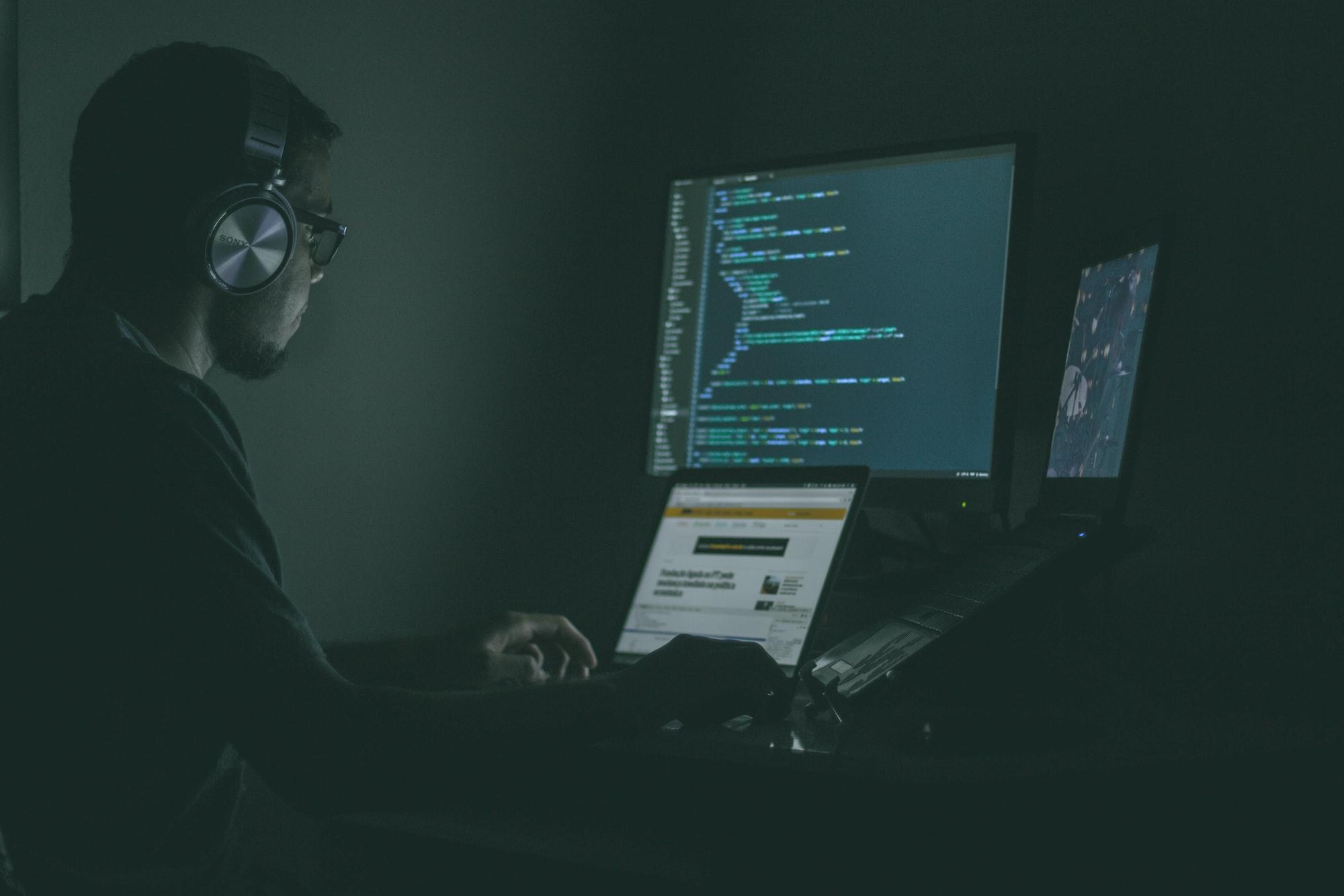 Homem sentado em frente à três telas de computador, com um headphone e óculos, estudando programação em um ambiente escuro.