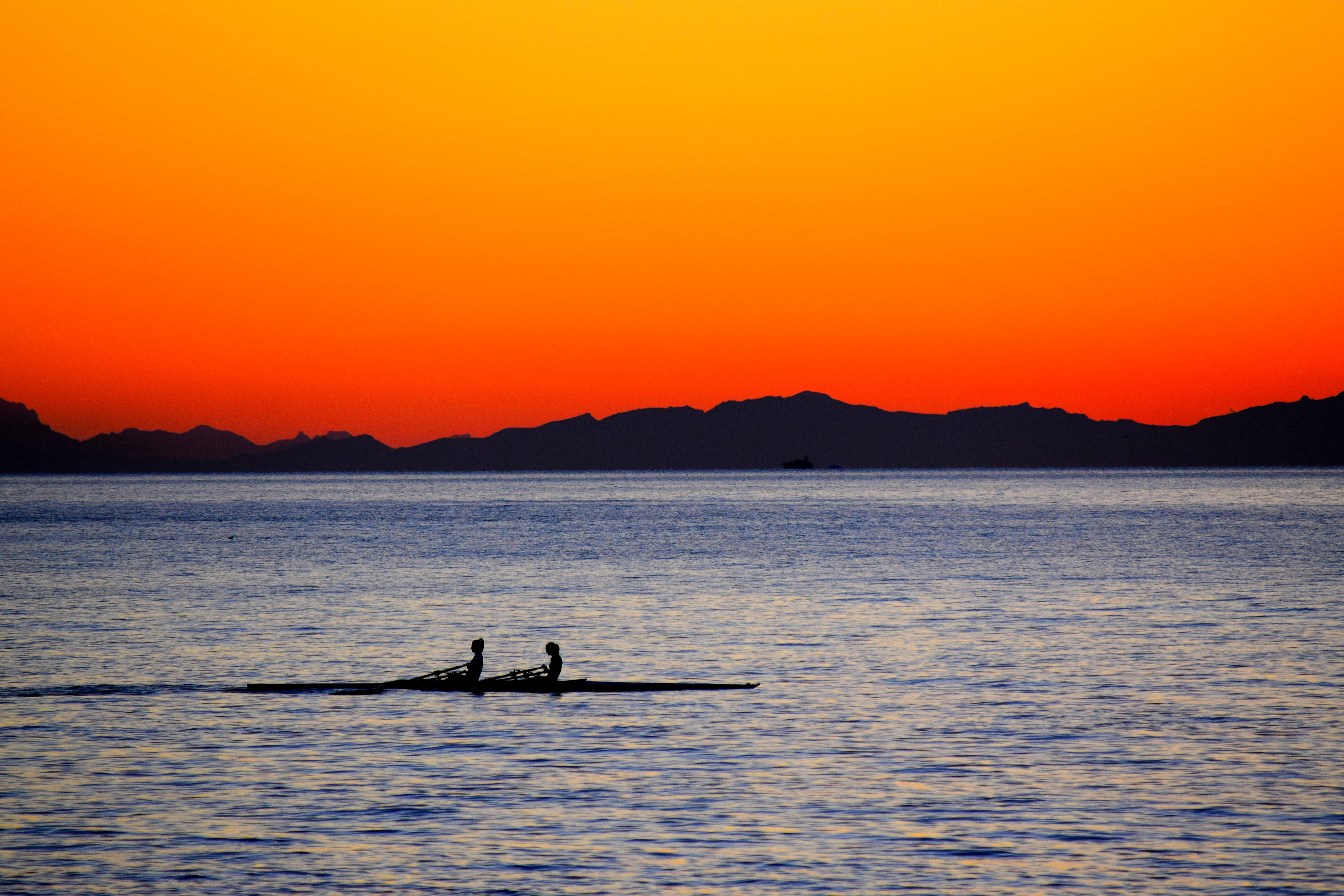 silhouette of two persons on boat during sunset