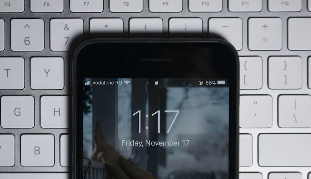 black iPhone on gray computer keyboard