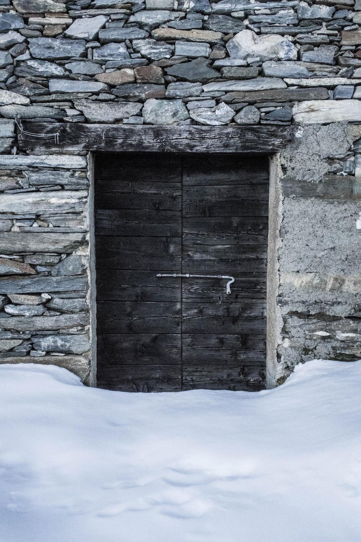 two black wooden doors behind snow