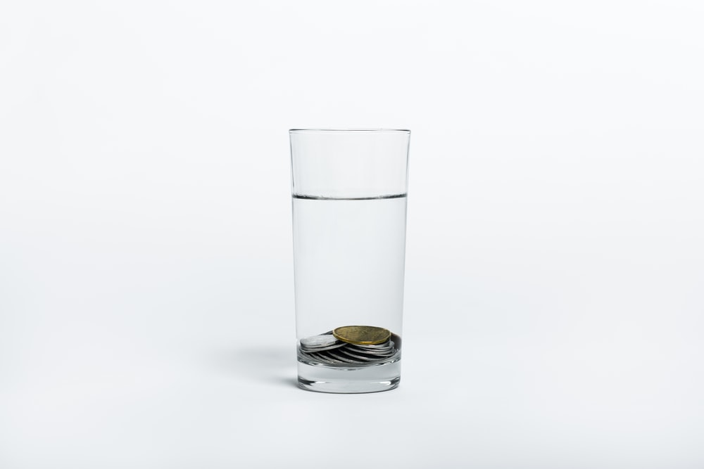 coins on clear drinking glass with water