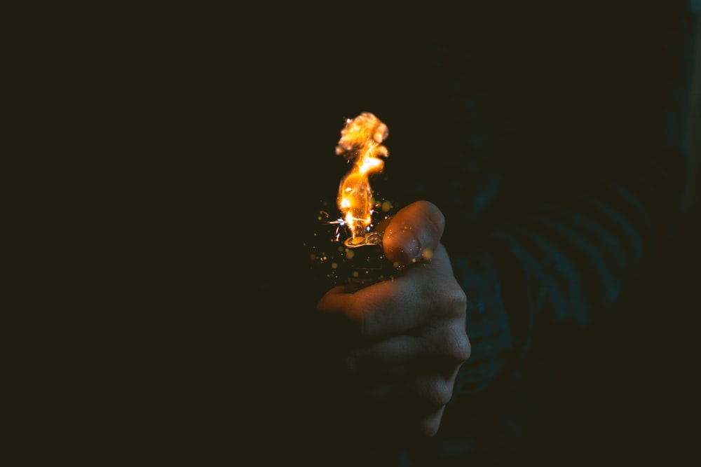 person holding lighted lighter