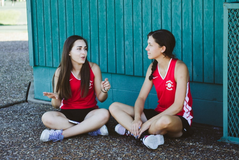 woman in red Nike tank top sitting beside woman in red tank top
