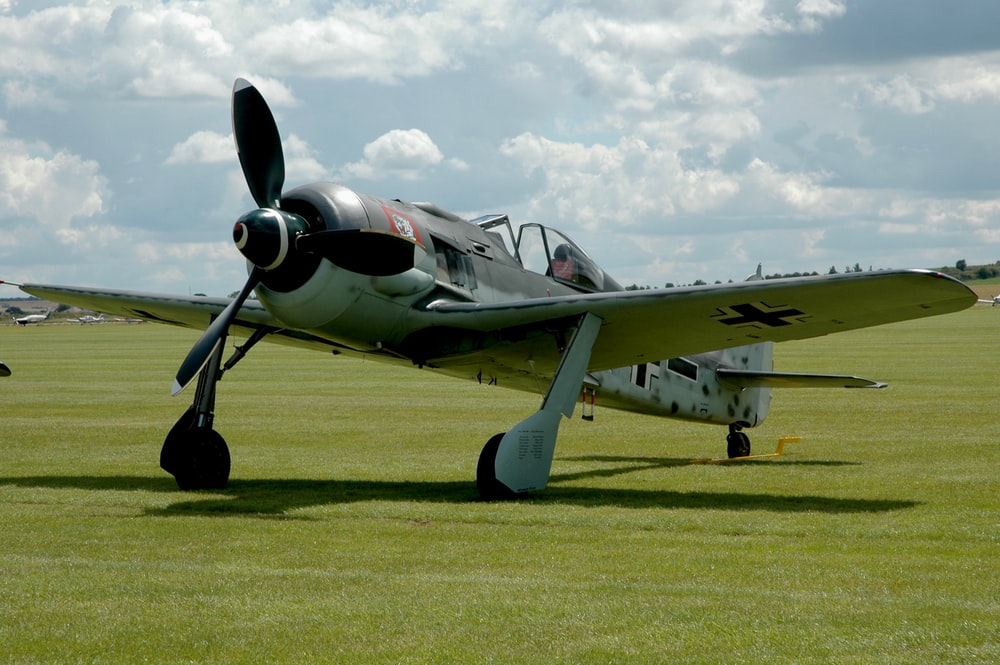 German gray BF 109 plane is parked on the green grass field