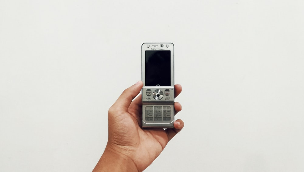 person holding gray candybar phone