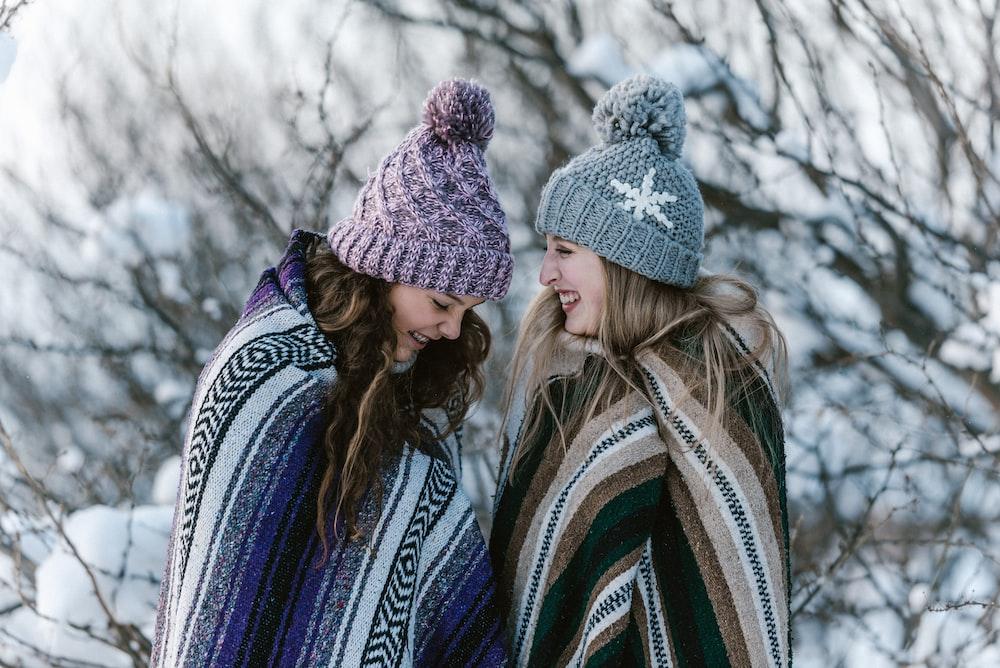 two women in multicolored striped blanket standing near tree